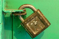 Candado viejo bloqueado del hierro en una puerta verde Imagen de archivo