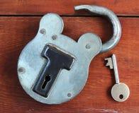 Candado viejo y clave en el fondo de madera Foto de archivo