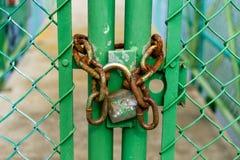Candado viejo y oxidado encadenado a una puerta verde en una cerca imagenes de archivo