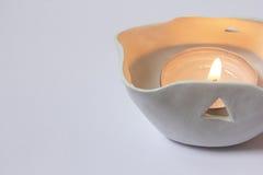 Candela alleggerita nel candeliere bianco sui precedenti bianchi immagine stock libera da diritti