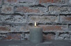 Candela bruciante davanti al muro di mattoni Fotografia Stock Libera da Diritti