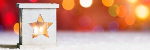 Candela bruciante in neve, con il bokeh delle luci di natale Insegna festiva di web di Natale Fotografia Stock Libera da Diritti
