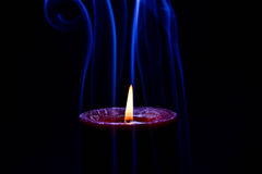 Candela bruciante rossa con fumo colorato blu immagine stock