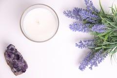 Candela dell'aroma in vetro con i fiori e l'ametista della lavanda fotografia stock