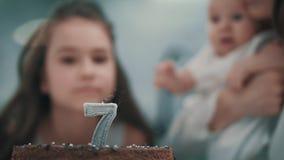 Candela di salto della ragazza sulla torta di compleanno alla festa di famiglia Buon compleanno del bambino stock footage