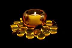 Candela di Tealight in supporto ambrato con i branelli Immagine Stock Libera da Diritti