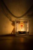 Candela di vetro con la renna sulla tavola di legno fotografie stock libere da diritti
