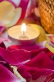 Candela e petali Immagini Stock