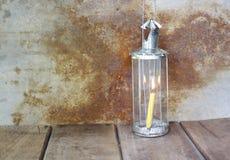 Candela nella luce di una lampada d'annata sulla tavola di legno Immagine Stock Libera da Diritti