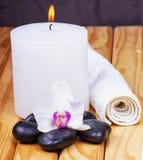 Candela, orchidea, pietre ed asciugamano immagine stock
