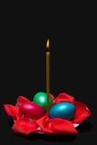Candela, petali rosa e tre uova di Pasqua Su un piatto, isolato Immagine Stock Libera da Diritti