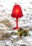 Candela rossa di Natale con i rami ed i coni dell'abete nell'inverno fotografie stock