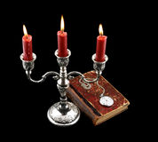 Candelabra, candles and old book with watch Stock Images