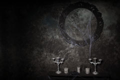 Candelabras and Ornate Frame Covered in Cobwebs. Candelabras and Empty Ornate Frame Covered in Cobwebs on Table in Eerie Halloween Haunted House Setting Royalty Free Stock Images