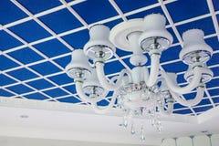 Candelabro de vidro no teto Teto azul à moda, dividido em quadrados Fotos de Stock Royalty Free