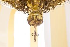 Candelabro em uma igreja com uma cruz A luz do contraste da janela ilumina o candelabro Fotografia de Stock Royalty Free