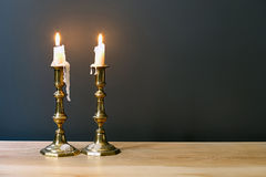 Candelabros retros con las velas ardientes en sitio minimalista Imagen de archivo libre de regalías