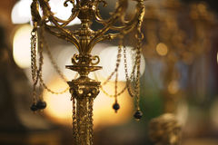 Candelabrum. Antique gilded candelabrum, decorated with chains in the antiquarian salon interior Stock Images