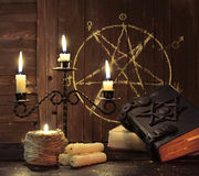 Candelabrum with books and pentagram. Magic candelabrum with burning candles and witch books on pentagram background. Black magic ritual with occult, evil and stock images