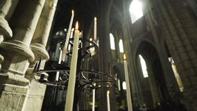 Candelabrum with burning candles. Interior of ancient Cathedral. Slow motion panoram from bottom to top vintage candelabrum with burning candles at background stock footage