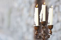 Candelabrum with three candles on grey background royalty free stock photo
