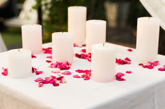 Candele bianche circondate con i petali rosa rosa Fotografia Stock