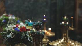Candele brucianti in candelieri e fiori nell'interno della chiesa all'interno video d archivio