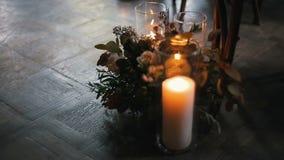 Candele brucianti con il bello mazzo dei fiori differenti vicino ad una sedia archivi video