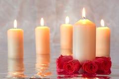 Candele brucianti con le rose rosse nella priorità alta Immagini Stock