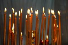 Candele brucianti della cera nei precedenti della chiesa Fotografie Stock Libere da Diritti