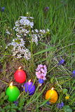 Candele brucianti delle uova di Pasqua nell'erba di primavera Fotografie Stock
