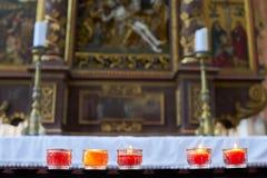 Candele brucianti nei supporti di candela variopinti in una chiesa Fotografie Stock