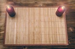 Candele brucianti sulla tavola di legno dello scrittorio con lo spazio della copia Fotografia Stock
