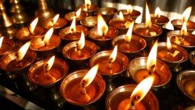 Candele Burning in tempiale Vista delle ciotole brillanti dorate con la fiamma di combustione delle candele dell'olio per culto archivi video