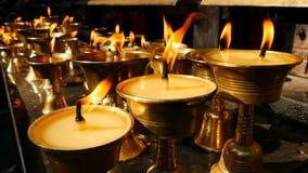 Candele Burning in tempiale Vista delle ciotole brillanti dorate con la fiamma di combustione delle candele dell'olio per culto video d archivio