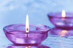 Candele in candelieri su un fondo metallico nella porpora fotografia stock