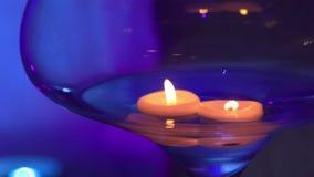 Candele che galleggiano in un vaso di vetro nella sera su un'illuminazione viola del fondo video d archivio