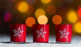 Candele che stanno nella neve con il bokeh arancio o dorato leggiadramente defocussed delle luci, nei precedenti Immagine Stock Libera da Diritti