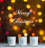 Candele che stanno nella neve con le luci leggiadramente defocussed, bokeh colourful nei precedenti, fondo festivo di Natale Immagine Stock