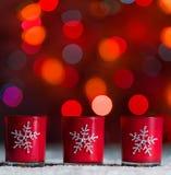 Candele che stanno nella neve con le luci leggiadramente defocussed, bokeh rosso nei precedenti, fondo festivo di Natale Fotografie Stock Libere da Diritti