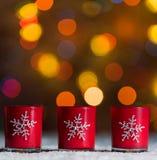Candele che stanno nella neve con le luci leggiadramente defocussed, bokeh rosso nei precedenti, fondo festivo di Natale Immagine Stock