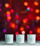 Candele che stanno nella neve con le luci leggiadramente defocussed, bokeh rosso nei precedenti, fondo festivo di Natale Fotografia Stock Libera da Diritti