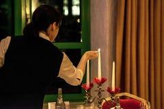 Candele del fulmine della donna sul banchetto con la regolazione rossa della tavola Fotografia Stock Libera da Diritti