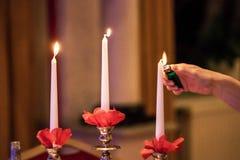 Candele del fulmine della mano della donna sul banchetto con la regolazione rossa della tavola Fotografia Stock Libera da Diritti
