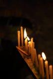 Candele di illuminazione sul fondo di buio del againt dell'altare Fotografia Stock