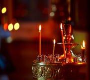 Candele di illuminazione in una chiesa Immagine Stock