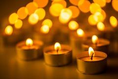 Candele di Natale che bruciano alla notte L'estratto esamina in controluce la priorità bassa Luce dorata della fiamma di candela Fotografie Stock