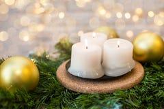 Candele di Natale su un ramo dell'abete e sulle palle di natale Fotografia Stock