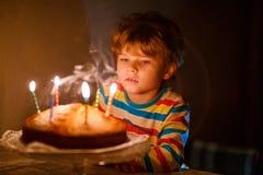 Candele di salto del ragazzo del bambino sulla torta di compleanno Fotografie Stock