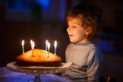 Candele di salto del ragazzo del bambino sulla torta di compleanno Immagini Stock